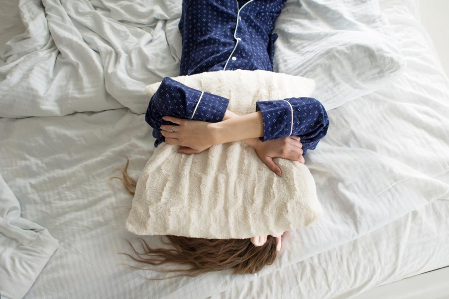 Woman with pillow on face